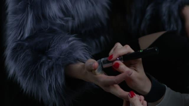 vídeos y material grabado en eventos de stock de detrás del escenario. make-up artist pone fundación en manos de la modelo. video de la moda. - esmalte de uñas rojo