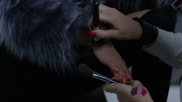 backstage. make-up artist puts foundation on model`s hands. fashion video. - make up brush stock videos and b-roll footage