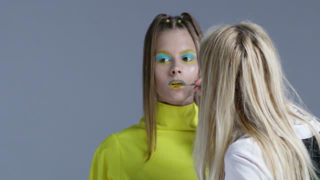 vídeos y material grabado en eventos de stock de detrás del escenario. make-up artist pone amarillo lápiz labial en los labios de la modelo. modelo lleva gafas de sol amarillo y grandes auriculares inalámbricos. video de la moda. - esmalte de uñas rojo
