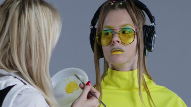 舞台裏。メイクアップ アーティストは、モデルの唇に黄色の口紅を置きます。モデルは、黄色いサングラスと大きなワイヤレス ヘッド フォンを着ています。ファッションのビデオ。 - メイクアップアーティスト点の映像素材/bロール