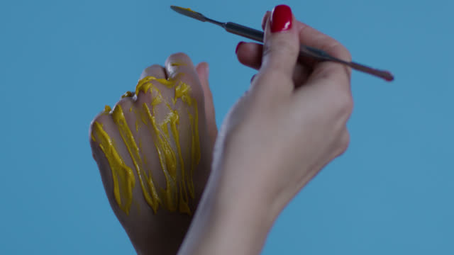 backstage. make-up artist puts yellow paint on fashion models`hands on blue background. fashion video. - greasepaint stock videos and b-roll footage