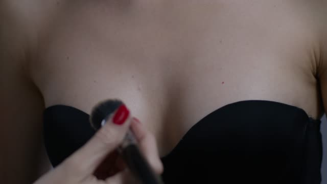 vídeos y material grabado en eventos de stock de backstage de un artista de maquillaje aplicando foundation en el pecho de la modelo de moda. video de la moda. - cuello parte de la vestimenta