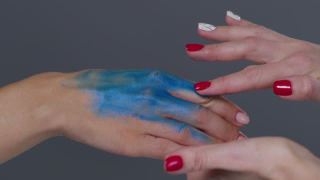 backstage of a make-up artist, putting blue glowing paint on model`s hand. fashion video. - putting stock videos and b-roll footage