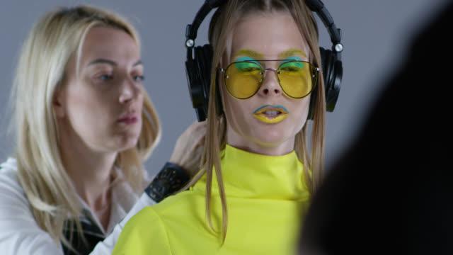 Hinter den Kulissen der Friseur Befestigung High-Fashion Model Haar. Model trägt gelbe Sonnenbrillen und schwarze Lederhandschuhe, große drahtlose Kopfhörer. Modell Gespräche zum Direktor. Mode-Video.