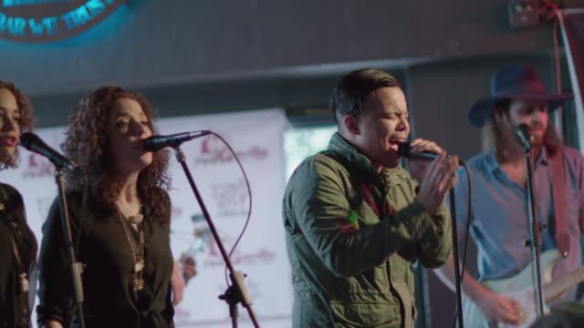 vídeos y material grabado en eventos de stock de backup singers sway and snap fingers with rock band in austin bar - performance group