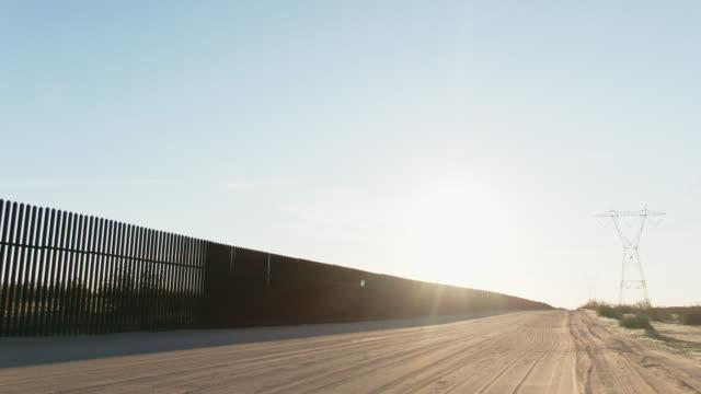明るく澄んだ晴れた日にメキシコと米国の間のスチールスラット国境の壁(米国側)の隣の未舗装道路に沿って後ろ向きに移動ドローンショット - 囲み塀点の映像素材/bロール