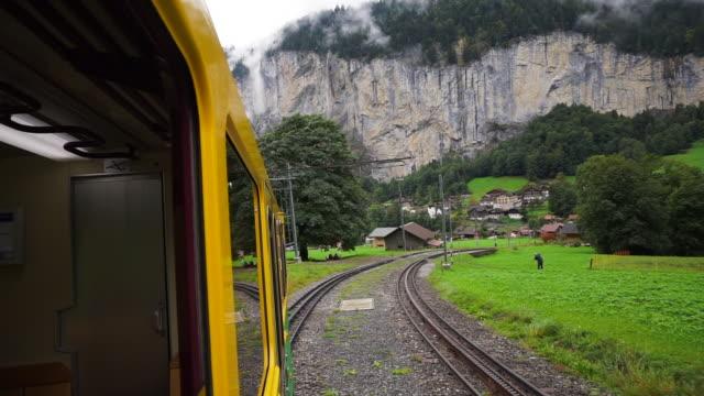 backward: passing through the rail road of kleine scheidegg switzerland - geländer stock-videos und b-roll-filmmaterial