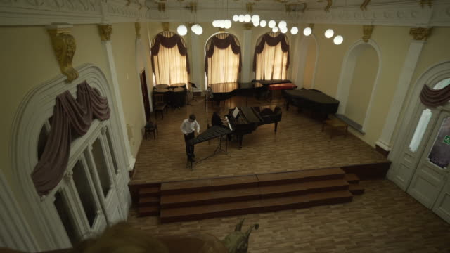 backward slow: watching musicians from the balcony do their thing with the piano and xylophone - kazan, russia - kazan russia stock videos and b-roll footage