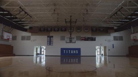 vídeos y material grabado en eventos de stock de backward tracking shot of an empty school gym. - ausencia