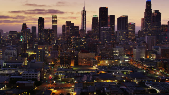 backwards aerial establishing shot of downtown la at twilight - city of los angeles stock videos & royalty-free footage
