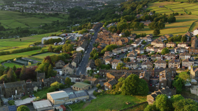 backwards aerial view of cross roads, west yorkshire on a summer evening - village stock videos & royalty-free footage