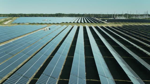 backwards drone flight across solar farm - power supply stock videos & royalty-free footage