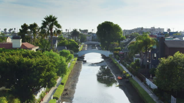 backwards drone flight along canal in venice canal historic district, los angeles - canal stock videos & royalty-free footage