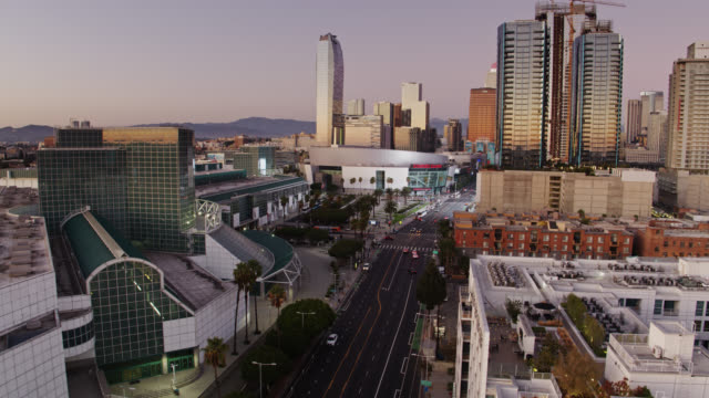 vídeos de stock e filmes b-roll de backwards drone flight along figueroa street looking towards los angeles convention center and la live - microsoft theater los angeles