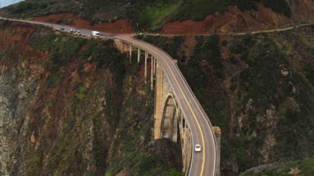 backwards drone flight of car driving over bixby creek bridge - bixby creek bridge stock videos & royalty-free footage