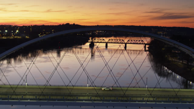 backwards drone flight over broadway bridge and arkansas river in little rock at sunset - arkansas stock videos & royalty-free footage