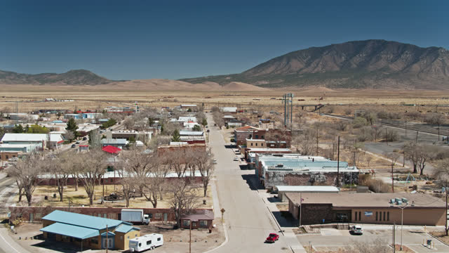 backwards drone flight over carrizozo, new mexico looking towards carrizo mountain - street name sign stock videos & royalty-free footage