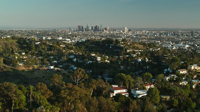 backwards drone flight over houses in the hollywood hills looking towards downtown la - city of los angeles stock videos & royalty-free footage