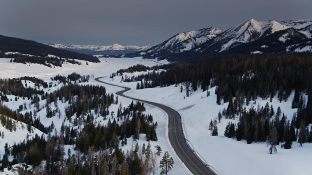 backwards drone flight over quiet road curving through bridger-teton national forest in winter - grand teton stock videos & royalty-free footage