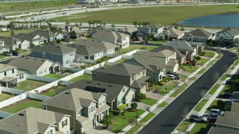 vidéos et rushes de vol de drone à l'envers au-dessus du logement suburbain près d'orlando - stéréotype de la classe moyenne