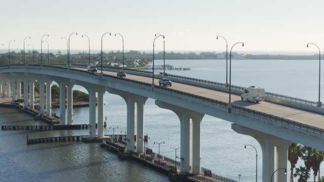 vidéos et rushes de backwards drone shot alongside causeway in jensen beach, florida - pont