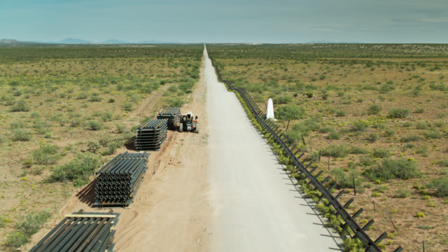 backwards drone shot of construction materials at us-mexico border - surrounding wall stock videos & royalty-free footage