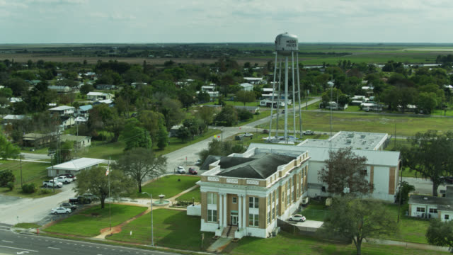 backwards drone shot of county courthouse, police station and water tower in moore haven, florida - street name sign stock videos & royalty-free footage