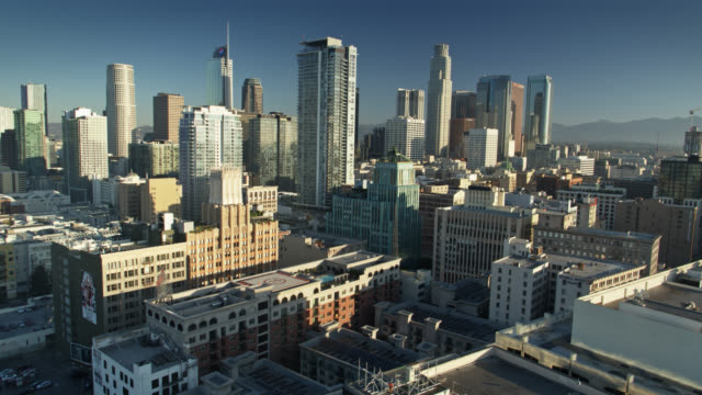vídeos de stock e filmes b-roll de backwards drone shot of dtla financial district from over the historic core - distrito financeiro