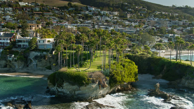 backwards drone shot of houses on either side of twin points in laguna beach - laguna beach california stock videos & royalty-free footage