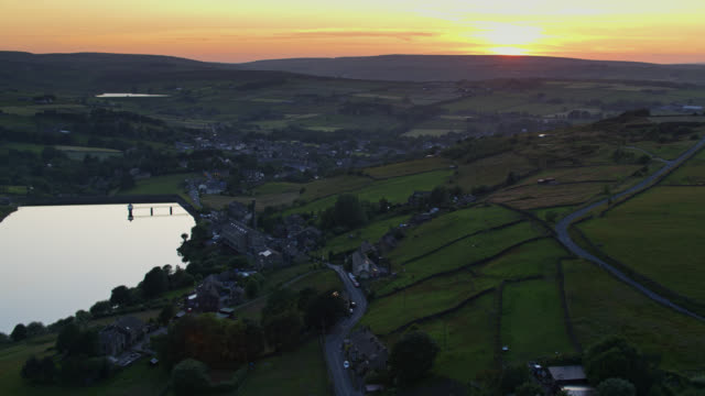backwards drone shot of leeming reservoir, oxenhope at sunset - pennines stock videos and b-roll footage