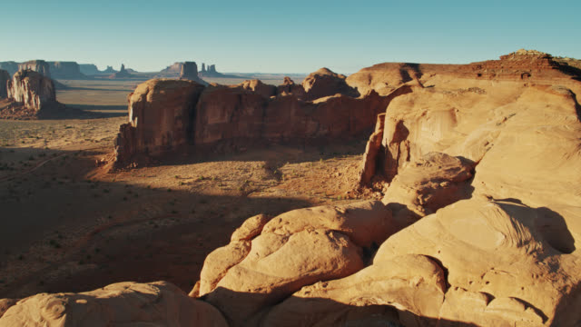 backwards drone shot of monument valley with mitten buttes in distance - mitten stock videos and b-roll footage