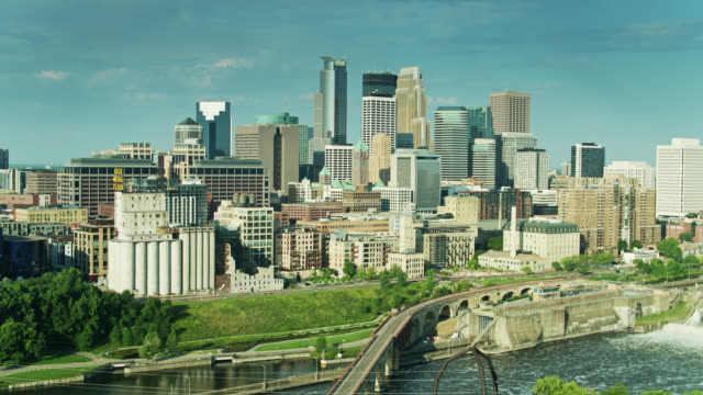 backwards drone shot of st. anthony falls historic district and downtown minneapolis revealing mississippi river - arch bridge stock videos & royalty-free footage