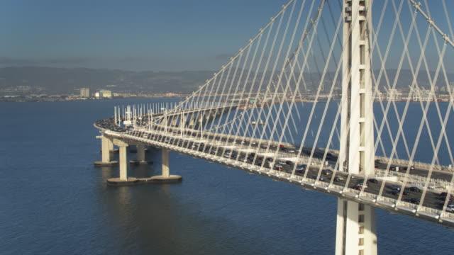 backwards drone shot of traffic leaving oakland on the bay bridge - oakland california stock videos & royalty-free footage
