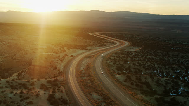 backwards drone shot of truck on i-70 in san rafael swell at sunset - american interstate stock videos & royalty-free footage