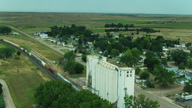 backwards drone shot over freight train passing grain elevator and small nebraska town - freight elevator stock videos & royalty-free footage