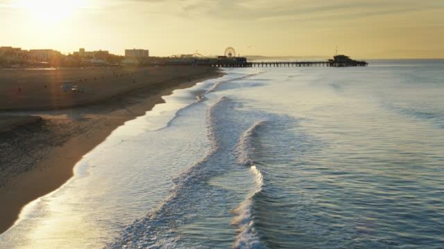 backwards drone shot over santa monica beach at dawn - santa monica stock videos & royalty-free footage