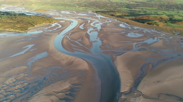 backwards flying aerial shot showing low tide in borth-y-gest, wales, united kingdom - low tide stock videos & royalty-free footage