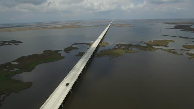 backwords tracking by causeway - Drone Aerial 4K Lake Pontchartrain CausewayGrand Isle Louisiana coast Mississippi river bridge and barge everglades, gulf delta, with wildlife 4K Transportation