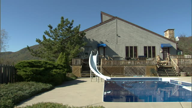 PAN Backyard of modern upscale rural home w/ open deck professionally landscaped landscaping inground pool w/ slide building by pool possibly summer...