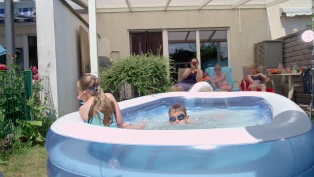 stockvideo's en b-roll-footage met backyard water fun cute little kids playing in zwembad slow motion - 10 11 jaar