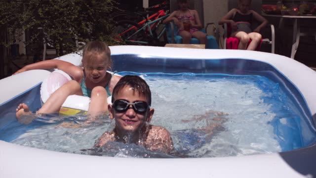 vídeos de stock, filmes e b-roll de quintal água diversão crianças fofas brincando na piscina super câmera lenta 1000 fps - óculos de natação