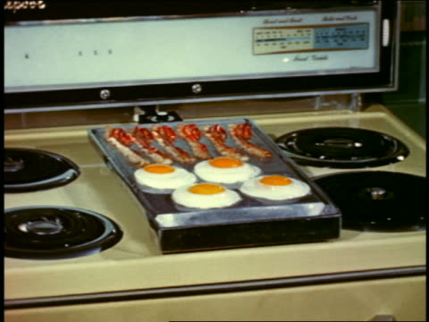 1958 bacon + eggs grilling on stovetop metallic griddle attachment - グリルパン点の映像素材/bロール