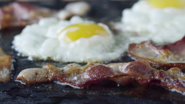 cu pan bacon rashers and eggs on frying pan / orem, utah, usa - prima colazione video stock e b–roll