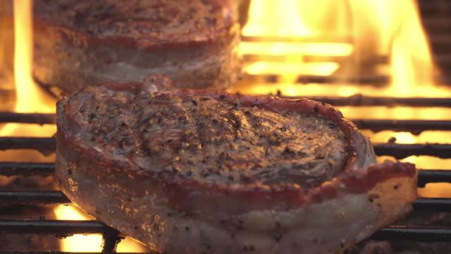 燃えるようなグリルの上フィレ肉ステーキのベーコン巻き - 低炭水化物ダイエット点の映像素材/bロール