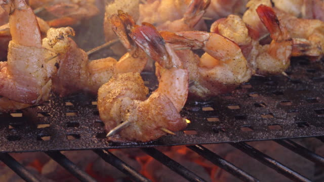 vídeos de stock e filmes b-roll de bacon wrapped jumbo shrimp or prawns on a grill - marisco