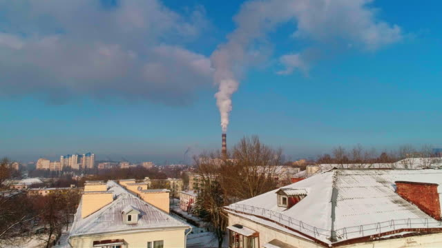 bad ecology. the thermal power plant located in the center of the residential district, throws out smoke from the high pipe, polluting the atmosphere of the city. aerial drone video with descending camera motion. - belarus stock videos & royalty-free footage