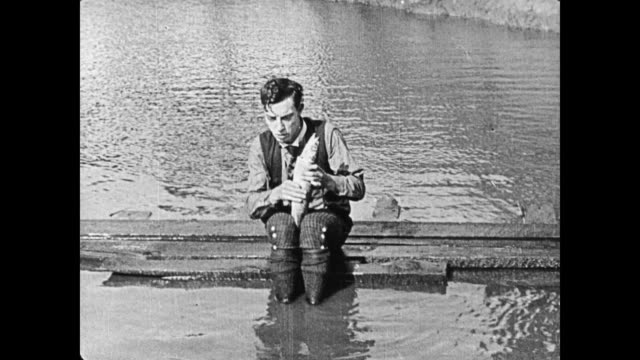 1920 bad golfer (buster keaton) tries to hit ball out of water hazard - spanking stock videos and b-roll footage