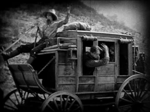 vidéos et rushes de b/w 1924 bad guy in stagecoach pushing face of person of person + winking / feature - 1924