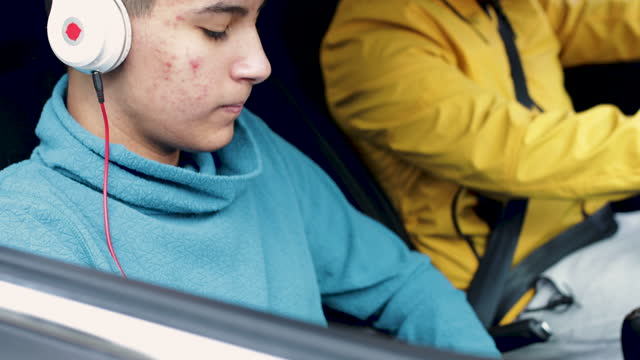vídeos de stock e filmes b-roll de bad mood teenage boy traveling in a car with his father - interior de carro