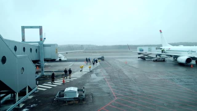 悪天候の日: 空港ターミナルから飛行機の搭乗階段まで歩く乗客。国際空港で乗客を乗り込ん - passenger点の映像素材/bロール